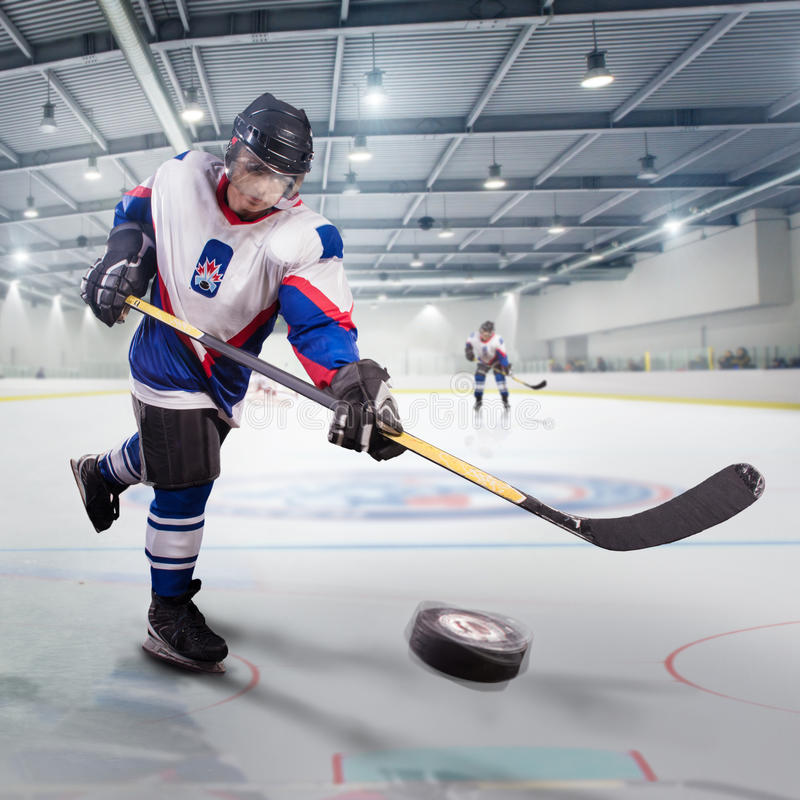Le joueur de hockey tire le galet et attaque le gardien de but image libre de droits