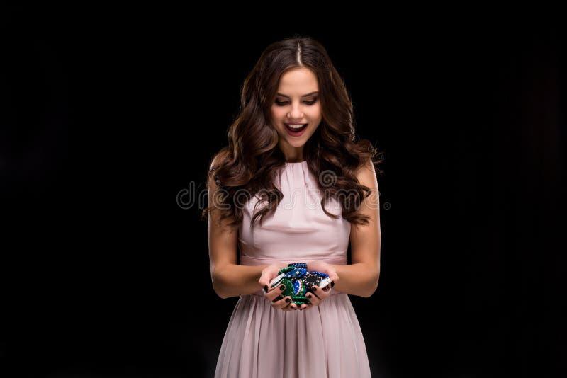 Le joueur de poker féminin avec des clous de noir de peinture tiennent ses jetons de poker pour faire un pari Jeu et concept d'af image stock