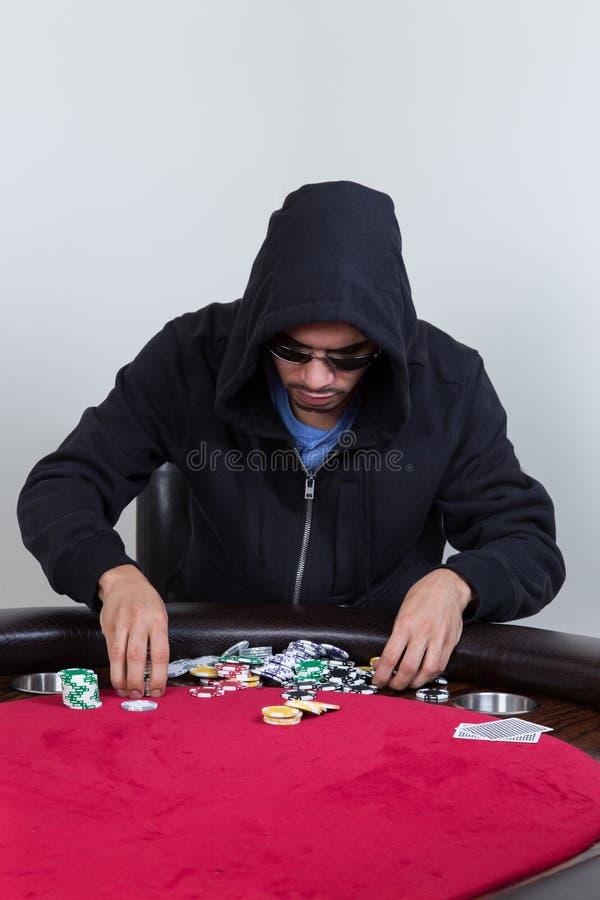 Le joueur de poker ratisse et empile des puces photographie stock libre de droits