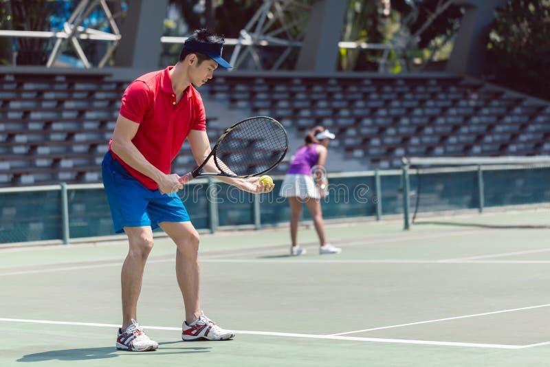 Le joueur de tennis asiatique prêt à servir au début de l'des doubles sont assortis photographie stock