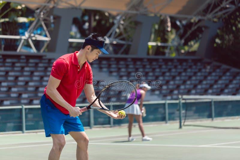 Le joueur de tennis asiatique prêt à servir au début de l'des doubles sont assortis images stock