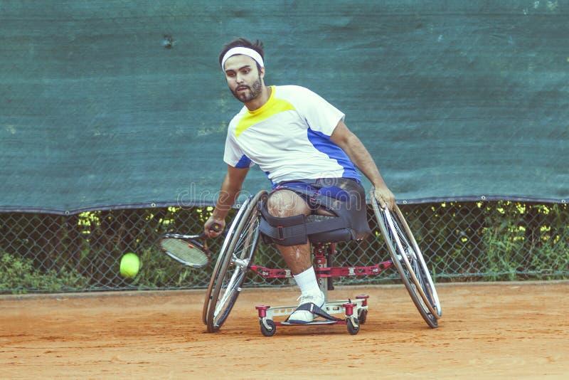 Le joueur de tennis handicapé frappe l'avant-main de boule image stock
