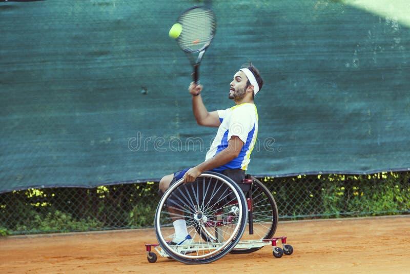 Le joueur de tennis handicapé frappe l'avant-main de boule images stock