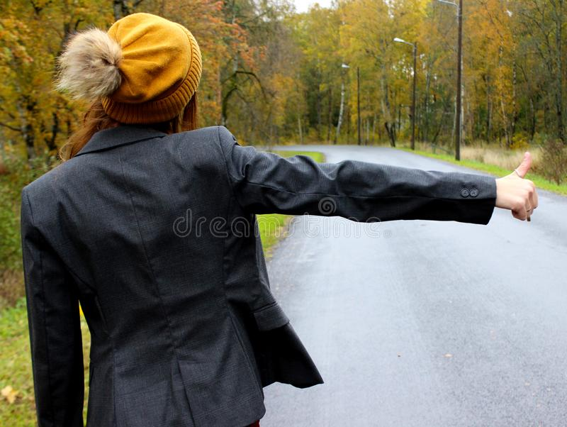 Le jour d'automne la voiture étée en panne et la fille dans une robe avec un chapeau attrape une autre voiture pour aider photo stock