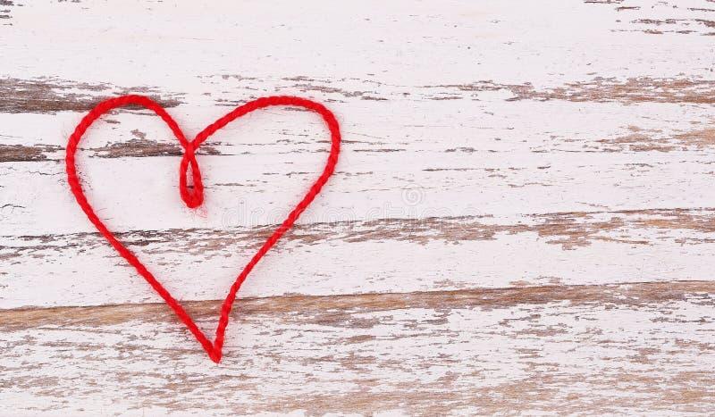 Le jour de Valentine Le coeur rouge du fil a formé sur le fond en bois photos stock