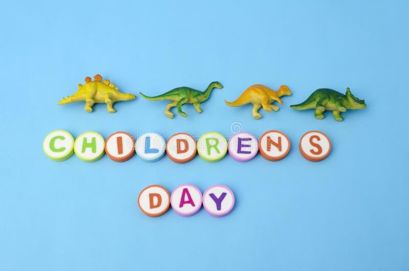 Le jour des enfants a fait à partir des lettres colorées et des jouets en plastique de dinosaure photo libre de droits