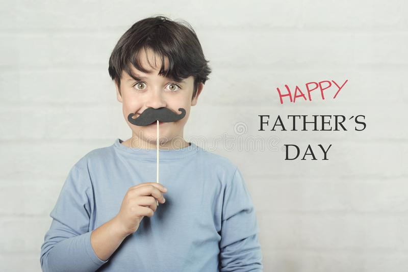 Le jour des father? heureux, gar?on avec la moustache fausse sur le b?ton images stock