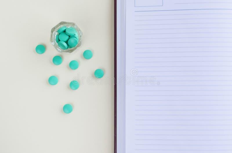 Le journal intime et les pilules, écrivent une recette, les pilules record, pilules dans une tasse en verre Copiez l'espace image libre de droits