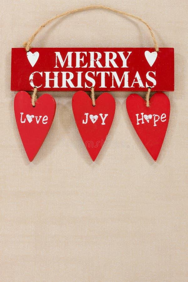 Le Joyeux Noël en bois se connectent un fond texturisé pâle avec l'espace pour la copie photo libre de droits