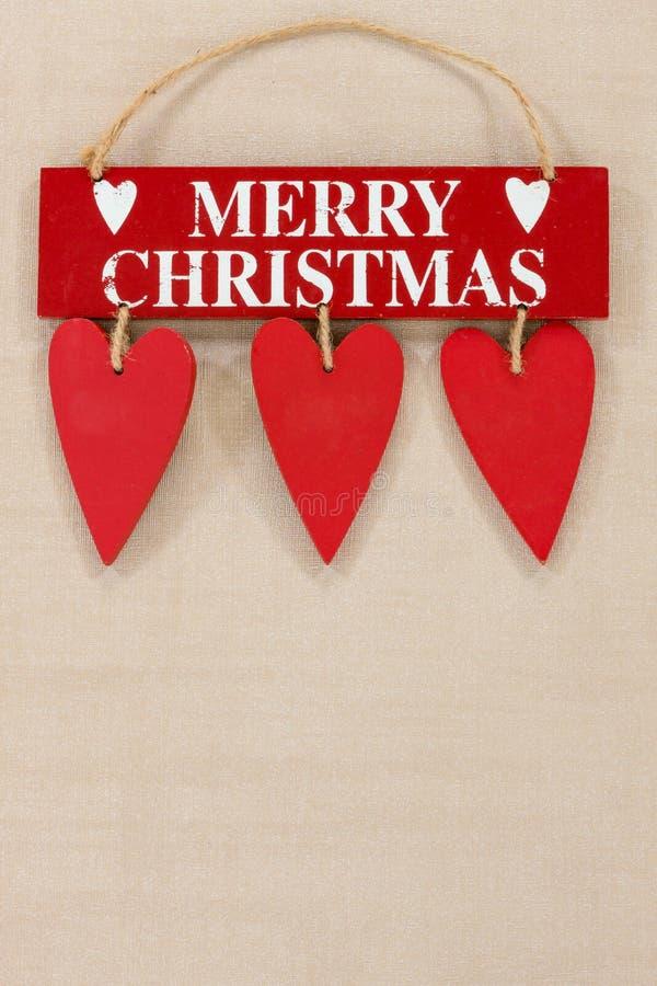 Le Joyeux Noël en bois se connectent un fond texturisé pâle avec l'espace pour la copie photographie stock libre de droits