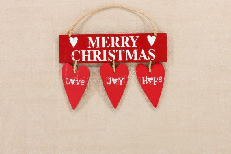 Le Joyeux Noël en bois se connectent un fond texturisé pâle avec l'espace pour la copie photos stock