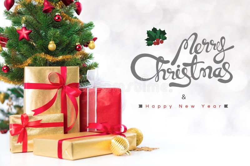 Le Joyeux Noël et la bonne année textotent avec des boîte-cadeau et l'orna photo stock