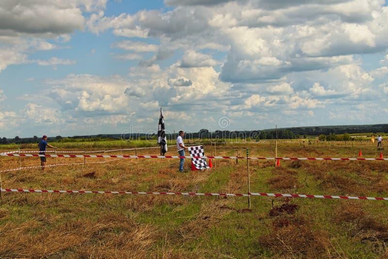 Le juge avec le grand drapeau à carreaux attend le cavalier Figure la concurrence de pilotage au champ photos stock