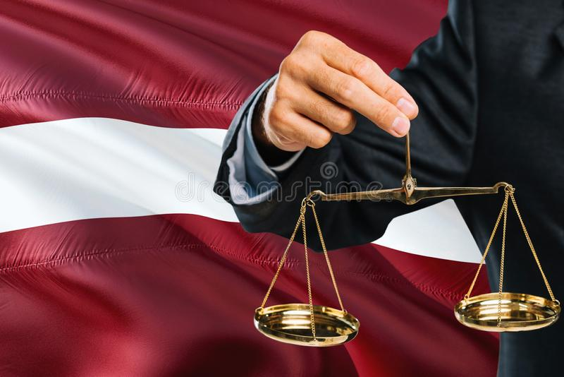 Le juge letton tient les échelles d'or de la justice avec le fond de ondulation de drapeau de la Lettonie Thème d'égalité et conc photo stock