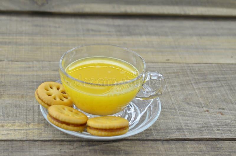 Le jus d'ananas serré avec des biscuits bloquent sur la table en bois photos libres de droits