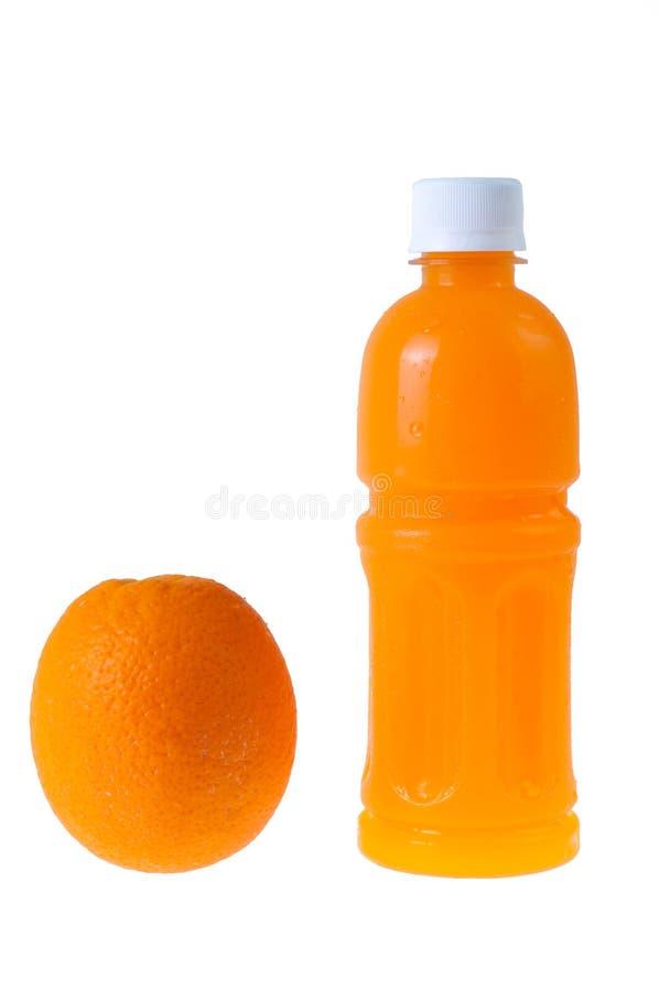 Le jus d'orange dans une bouteille et une orange à côté de lui a isolé sur le blanc photos stock