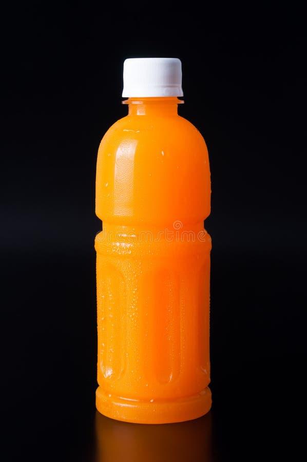 Jus d'orange dans une bouteille et une orange sur le noir image libre de droits