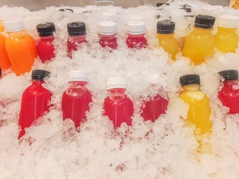 Le jus de légumes et le jus de fruit, ont mis une bouteille claire, imbibée en glace, fruit frais et jus de légumes pour le boire photographie stock