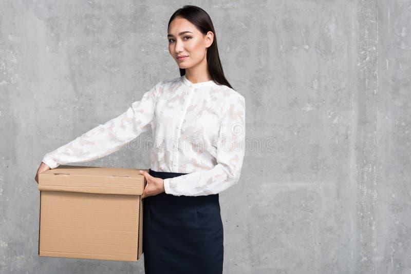 Le karriärflickan som håller den stora lådan royaltyfri bild