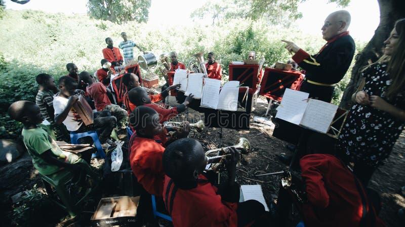 LE KENYA, KISUMU - 20 MAI 2017 : Concert d'une bande africaine avec un dessiccateur caucasien en plein air dans le jour ensoleill images libres de droits