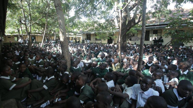 LE KENYA, KISUMU - 23 MAI 2017 : Grande foule des enfants africains dans l'uniforme se reposant sur un extérieur au sol près de l images libres de droits