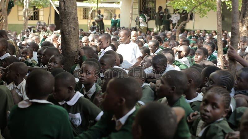 LE KENYA, KISUMU - 23 MAI 2017 : Grande foule des enfants africains dans l'uniforme se reposant sur un extérieur au sol près de l photographie stock libre de droits