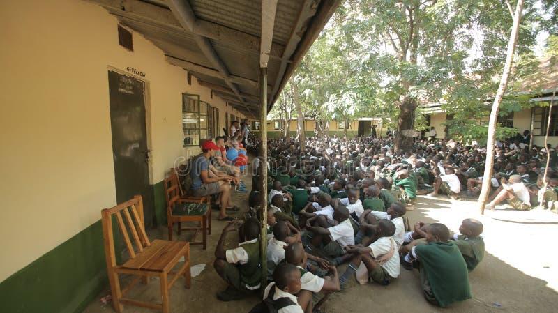 LE KENYA, KISUMU - 23 MAI 2017 : Grande foule des enfants africains dans l'uniforme se reposant sur un extérieur au sol près de l image stock