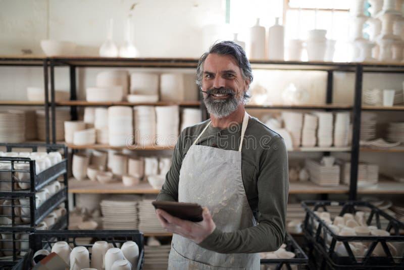 Le keramikern som använder minnestavlan som omges av arbete arkivfoto
