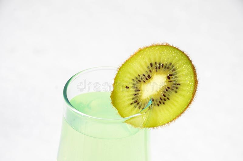 Le kiwi juteux de Skibka est ficelé sur un verre de vin avec du jus images stock