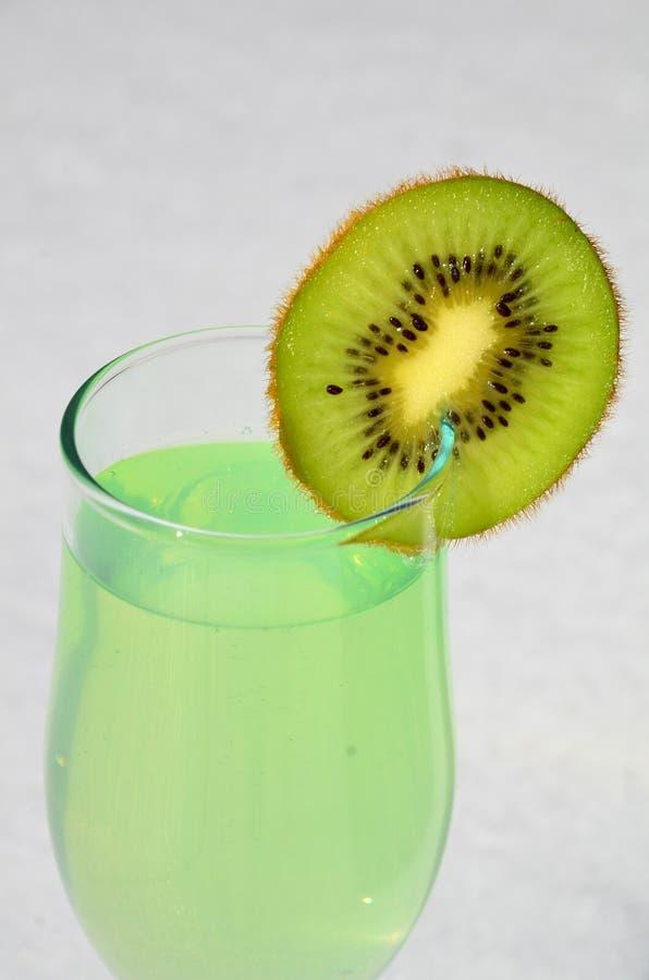 Le kiwi juteux de Skibka est ficelé sur un verre de vin avec du jus image stock