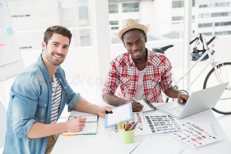 Le kollegor som arbetar med minnestavlan och bärbara datorn arkivbilder