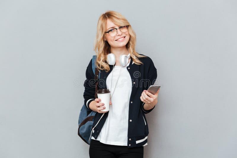 Le koppen kaffe och smartphonen för kvinnlig student den hållande royaltyfri bild