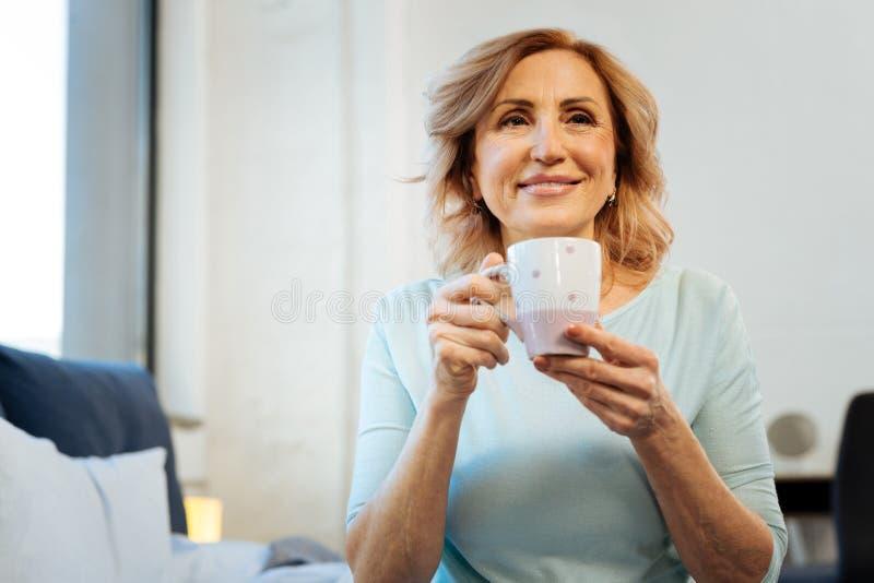 Le kort-haired mogna damen som den är lycklig med hennes fridsamma morgon fotografering för bildbyråer