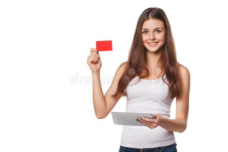 Le kreditkorten för kvinnavisningmellanrumet rym minnestavlaPC:n i hand, i den vita t-skjortan som isoleras över grå bakgrund royaltyfri fotografi
