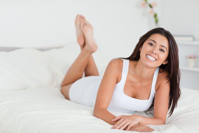Le kvinna som ligger på underlag med korsade ben royaltyfri fotografi