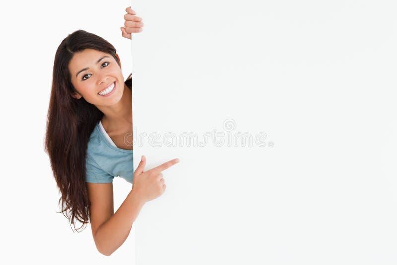 Le kvinna som pekar på ett bräde royaltyfri fotografi
