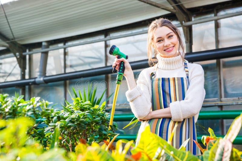 Le kvinnaanseende i trädgårds- slang för orangeri och för innehav royaltyfria bilder