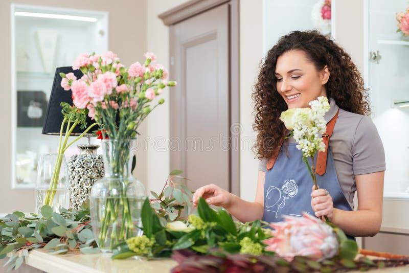Le kvinnablomsterhandlareanseende och danandebuketten i blomsterhandel arkivbild