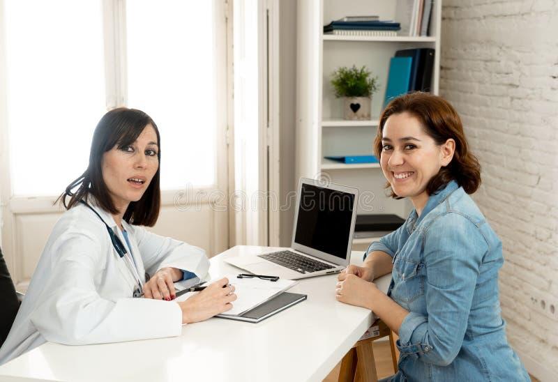 Le kvinnadoktorsspecialisten som har konsultation genom att använda bärbara datorn för att informera den lyckliga patienten royaltyfri fotografi