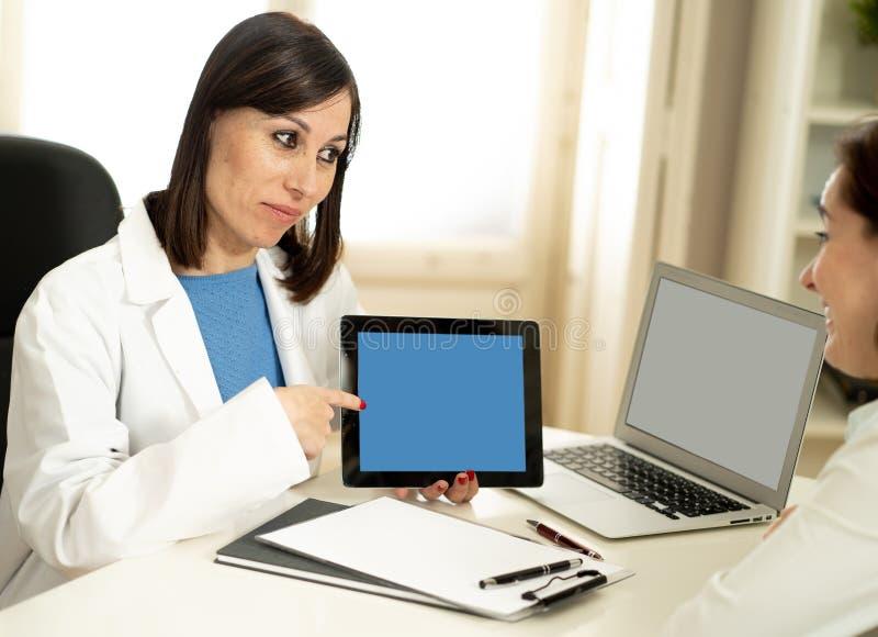 Le kvinnadoktorsspecialisten som har konsultation genom att använda den digitala minnestavlan för att informera patienten royaltyfri bild