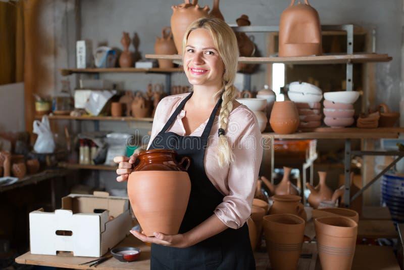Le kvinnakeramikern som bär keramiska skyttlar fotografering för bildbyråer