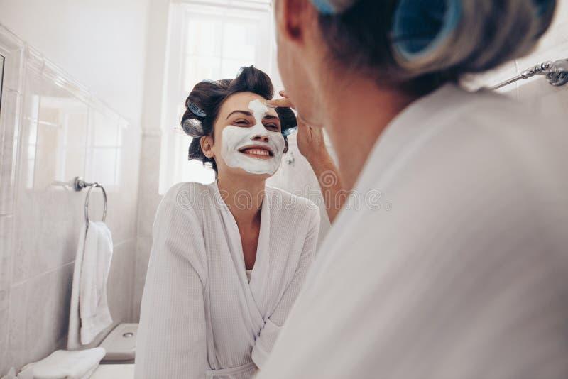 Le kvinnan i badrocken som får hennes ansiktsbehandling gjord hemma Två kvinnor som står i badrum med lockiga rullar som klämmas  royaltyfria foton
