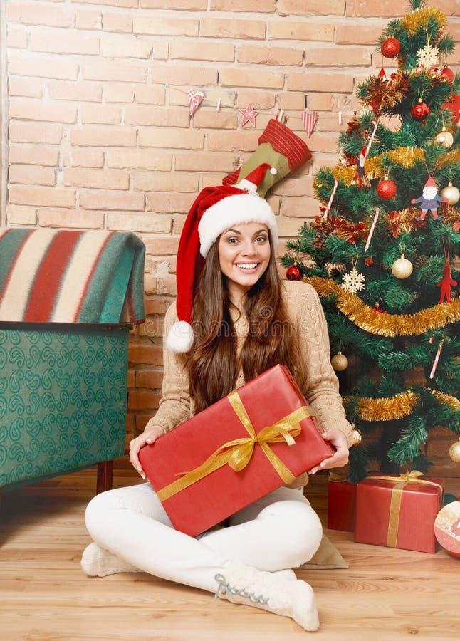 Le kvinnan i den santa hatten med sammanträde för gåvaask under julgranen royaltyfri foto