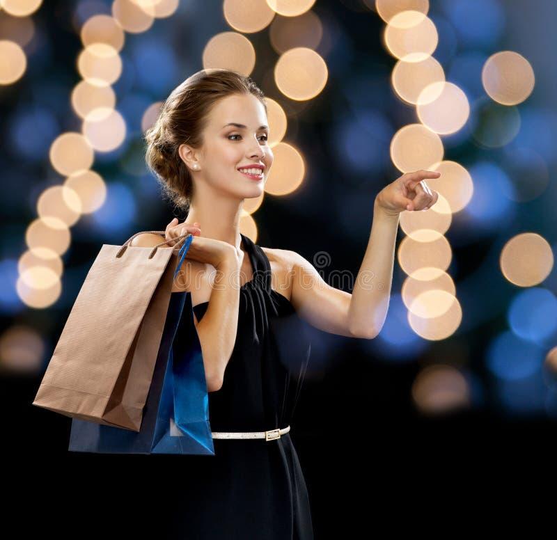 Le kvinnan i klänning med shoppingpåsar royaltyfria bilder