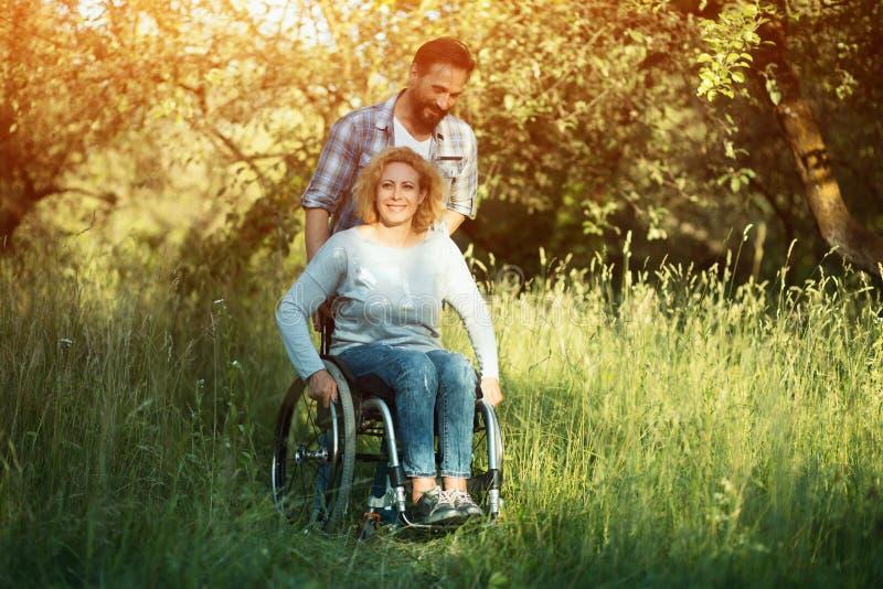 Le kvinnan i rullstol med maken i parkera på solig dag fotografering för bildbyråer