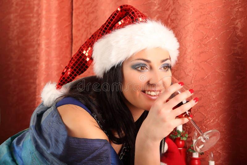 Le kvinnan i santa hjälpredahatt över vardagsrum med bakgrund för julträd royaltyfria bilder