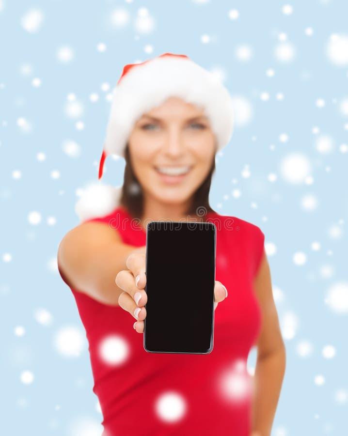 Le kvinnan i santa hjälpredahatt med smartphonen royaltyfri foto