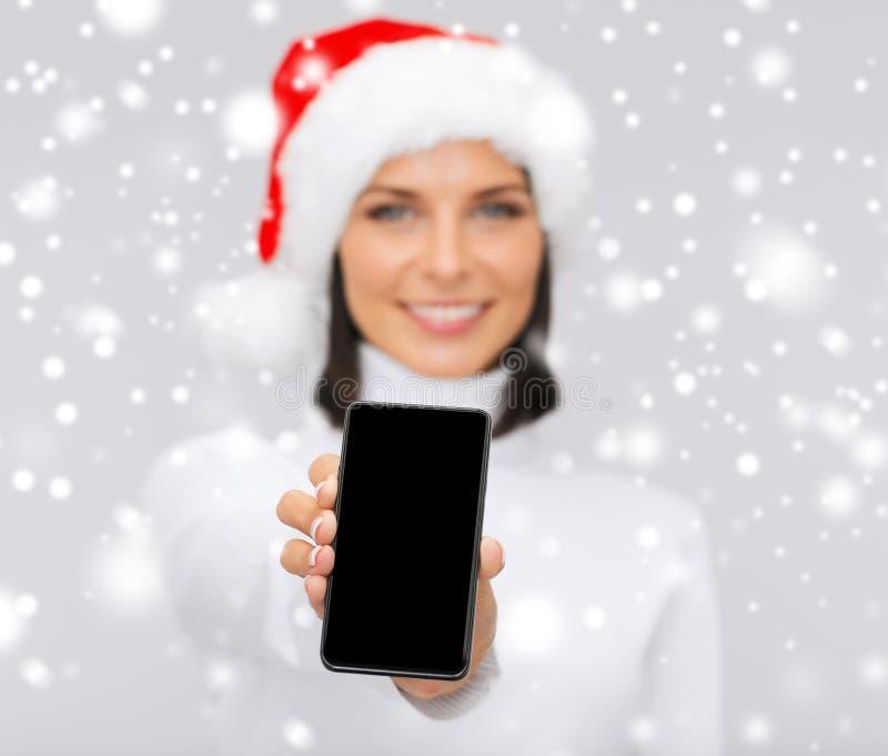 Le kvinnan i santa hjälpredahatt med smartphonen arkivbilder
