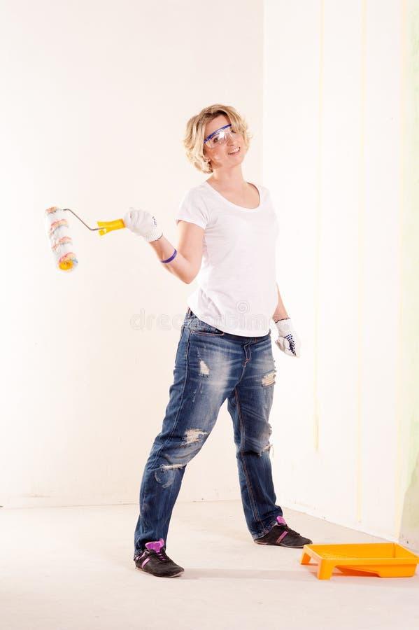 Le kvinnan i skyddande exponeringsglas med rullen borsta fotografering för bildbyråer