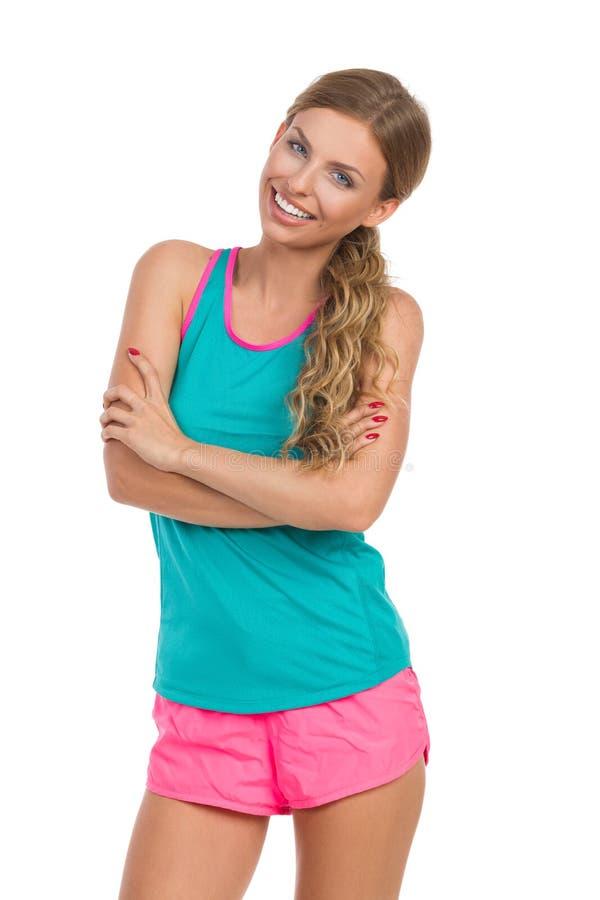 Le kvinnan i vibrerande sportkläder med korsade armar fotografering för bildbyråer